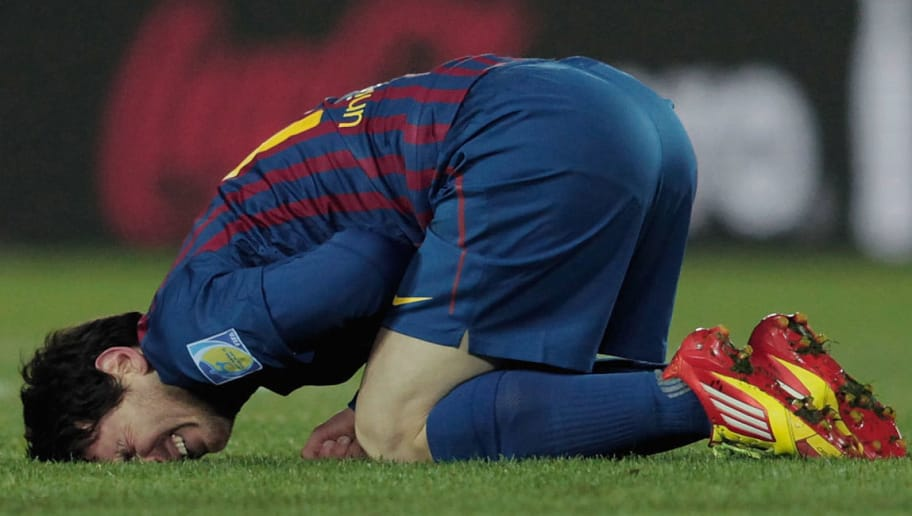 YOKOHAMA, JAPAN - DECEMBER 18: Lionel Messi of Barcelona lies injured during the FIFA Club World Cup Final match between Santosl and Barcelona at the Yokohama International Stadium on December 18, 2011 in Yokohama, Japan. (Photo by Lintao Zhang/Getty Images)