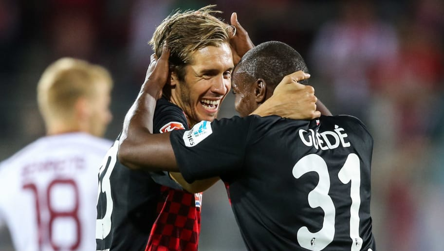 FREIBURG IM BREISGAU, GERMANY - JULY 27:  Julian Schuster (L) and Karim Guede (R) of Freiburg celebrate winning with team mates after the 2. Bundesliga match between SC Freiburg and 1. FC Nuernberg at Schwarzwald-Stadion on July 27, 2015 in Freiburg im Breisgau, Germany.  (Photo by Simon Hofmann/Bongarts/Getty Images)
