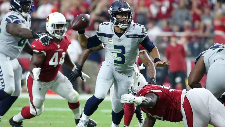 GLENDALE, AZ - SEPTEMBER 30:  Quarterback Russell Wilson #3 of the Seattle Seahawks looks to throw the ball as he eludes the tackle of defensive lineman Rodney Gunter #95 of the Arizona Cardinals during an NFL game at State Farm Stadium on September 30, 2018 in Glendale, Arizona.  (Photo by Ralph Freso/Getty Images)
