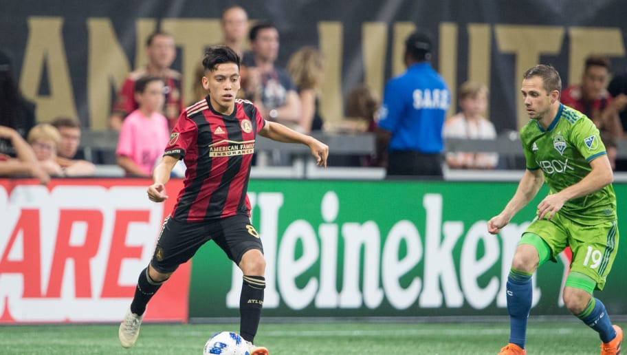 ATLANTA, GA - JULY 15: Ezequiel Barco #8 of Atlanta United looks to maneuver the ball by Harry Shipp #19 of Seattle Sounders FC 2 during the game at Mercedes-Benz Stadium on July 15, 2018 in Atlanta, Georgia.  (Photo by Michael Chang/Getty Images)
