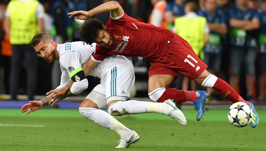 TOPSHOT - Liverpool's Egyptian forward Mohamed Salah (R) falls with Real Madrid's Spanish defender Sergio Ramos leading to Salah being injured during the UEFA Champions League final football match between Liverpool and Real Madrid at the Olympic Stadium in Kiev, Ukraine, on May 26, 2018. (Photo by GENYA SAVILOV / AFP)        (Photo credit should read GENYA SAVILOV/AFP/Getty Images)