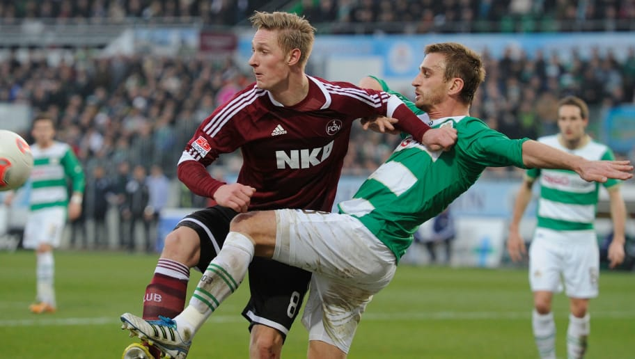 FUERTH, GERMANY - NOVEMBER 24:  Milorad Pekovic (R) of Fuerth challenges Sebastian Polter of Nuernberg during the Bundesliga match between SpVgg Greuther Fuerth and 1. FC Nuernberg at Trolli-Arena on November 24, 2012 in Fuerth, Germany.  (Photo by Lennart Preiss/Bongarts/Getty Images)