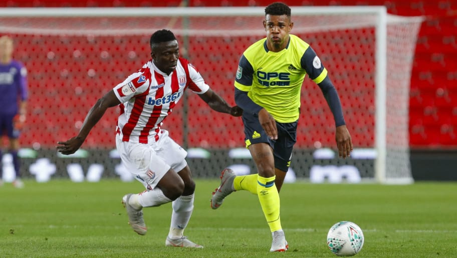 STOKE ON TRENT, ENGLAND - AUGUST 28: Juninho Bacuna of Huddersfield Town takes on Peter Etebo of Stoke City during the Carabao Cup Second Round match between Stoke City and Huddersfield Town at Bet365 Stadium on August 28, 2018 in Stoke on Trent, England. (Photo by John Early/Getty Images)