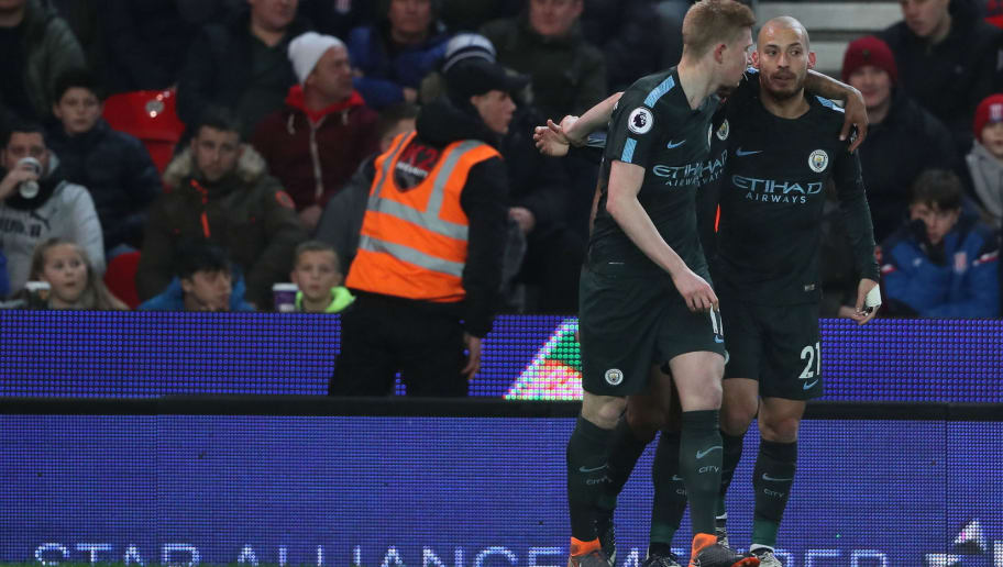 STOKE ON TRENT, ENGLAND - MARCH 12: David Silva of Manchester City celebrates with Kevin De Bruyne of Manchester City after scoring a goal to make it 1-0 during the Premier League match between Stoke City and Manchester City at Bet365 Stadium on March 12, 2018 in Stoke on Trent, England. (Photo by Matthew Ashton - AMA/Getty Images)