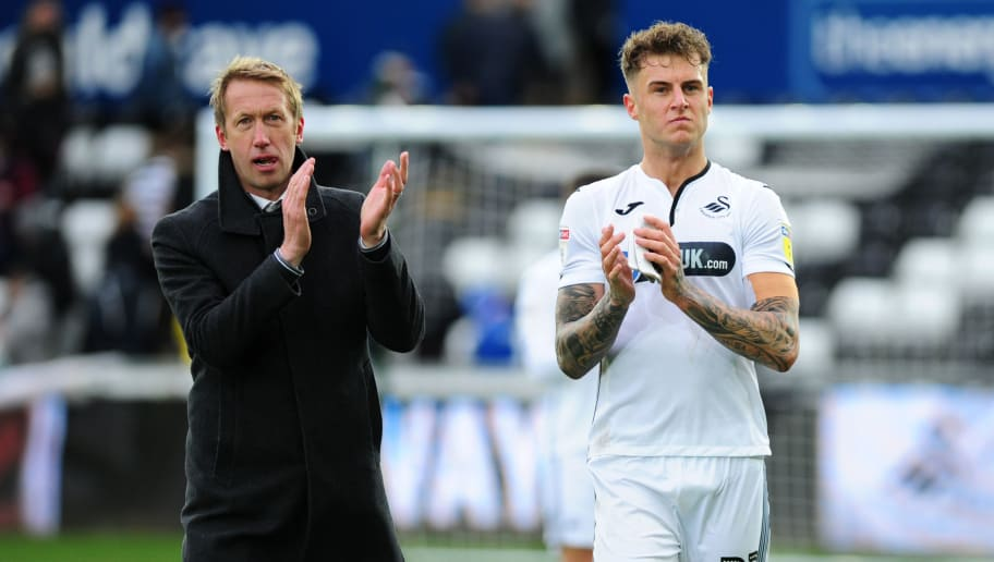SWANSEA, WALES - OCTOBER 27: Graham Potter Manager of Swansea City speaks with Joe Rodon of Swansea City during the Sky Bet Championship match between Swansea City and Reading at the Liberty Stadium on October 27, 2018 in Swansea, Wales. (Photo by Athena Pictures/Getty Images)