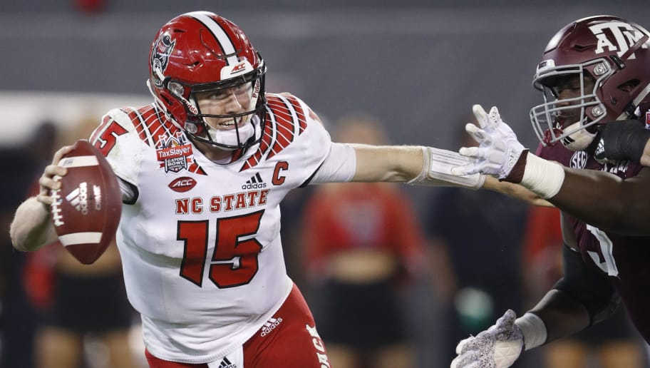 JACKSONVILLE, FL - DECEMBER 31: Ryan Finley #15 of the North Carolina State Wolfpack tries to avoid pressure while looking to pass against the Texas A&M Aggies in second half of the TaxSlayer Gator Bowl at TIAA Bank Field on December 31, 2018 in Jacksonville, Florida. Texas A&M won 52-13. (Photo by Joe Robbins/Getty Images)