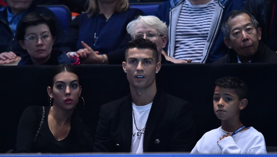 Juventus' Portuguese forward Cristiano Ronaldo (C) sits with Georgina Rodriguez (L) and his son Cristiano Jnr as they watch Serbia's Novak Djokovic plays against US player John Isner in their men's singles round-robin match on day two of the ATP World Tour Finals tennis tournament at the O2 Arena in London on November 12, 2018. (Photo by Glyn KIRK / AFP)        (Photo credit should read GLYN KIRK/AFP/Getty Images)