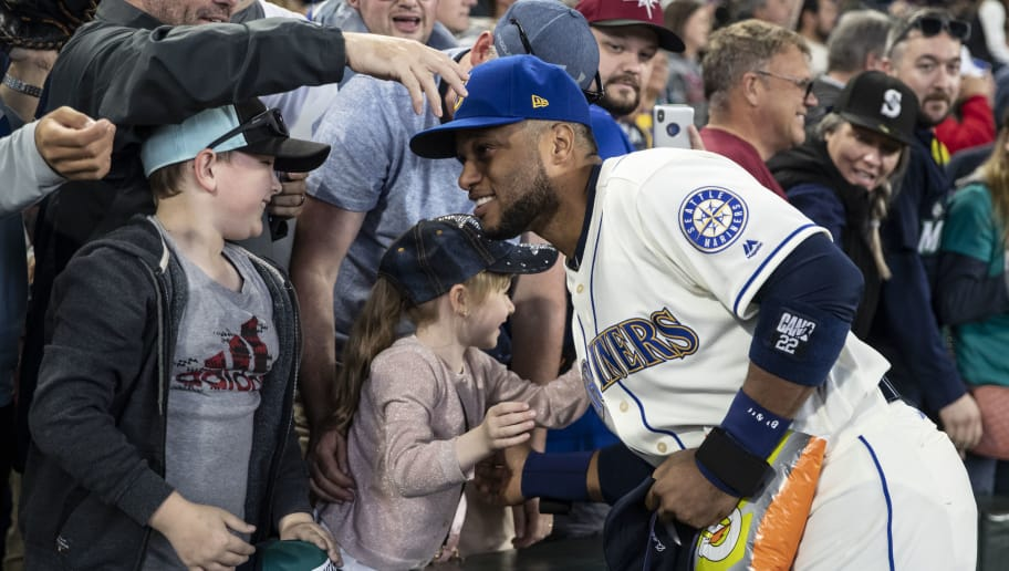 SEATTLE, WA - SEPTEMBER 30: Robinson Cano #22 of the Seattle Mariners hugs a young fan after a game against the Texas Rangers at Safeco Field on September 30, 2018 in Seattle, Washington. The Mariners won the game 3-1. (Photo by Stephen Brashear/Getty Images)