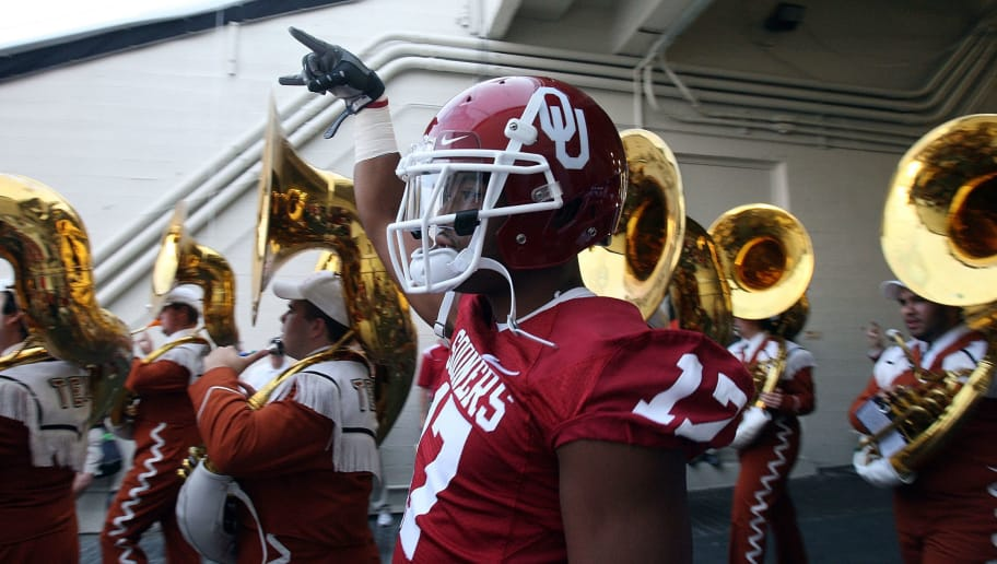 DALLAS - OCTOBER 11:  Running back Mossis Madu #17 of the Oklahoma Sooners gives a downward 'hook em horns' sign while walking to the field alongside the Texas Longhorns band at the Cotton Bowl on October 11, 2008 in Dallas, Texas.  (Photo by Ronald Martinez/Getty Images)