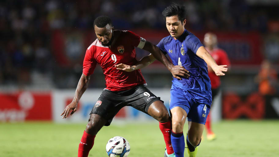 SUPHAN BURI, THAILAND - OCTOBER 14: Khaleem Hyland #9 of Trinidad and Tobago (L) is tackled by Chalermpong Kerdkaew #4 of Thailand (R) during the international friendly match between Thailand and Trinidad and Tobago at Suphanburi Stadium on October 14, 2018 in Suphan Buri, Thailand. (Photo by Pakawich Damrongkiattisak/Getty Images)