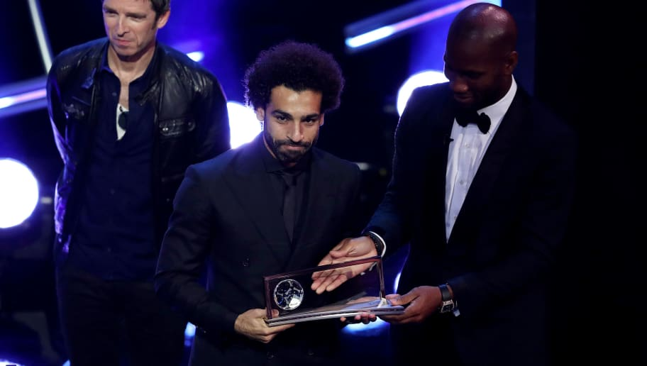 LONDON, ENGLAND - SEPTEMBER 24:  Former Ivorian footballer Didier Drogba (R) and Noel Gallagher present Mohamed Salah of Liverpool with the trophy for the FIFA Puskas Award 2018 during the The Best FIFA Football Awards Show at Royal Festival Hall on September 24, 2018 in London, England.  (Photo by Dan Istitene/Getty Images)
