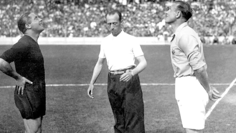 The captains of the French and Italian national soccer teams Etienne Mattler (R) and Giuseppe Meazza watch the coin toss as Belgian referee Louis Baert stands in the middle 12 June 1938 in Colombes, in the suburbs of Paris, before the start of the World Cup quarterfinal match between the two nations. (Photo credit should read STAFF/AFP/Getty Images)