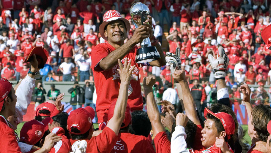 Toluca' Paulo Da Silva (C) raises the tr