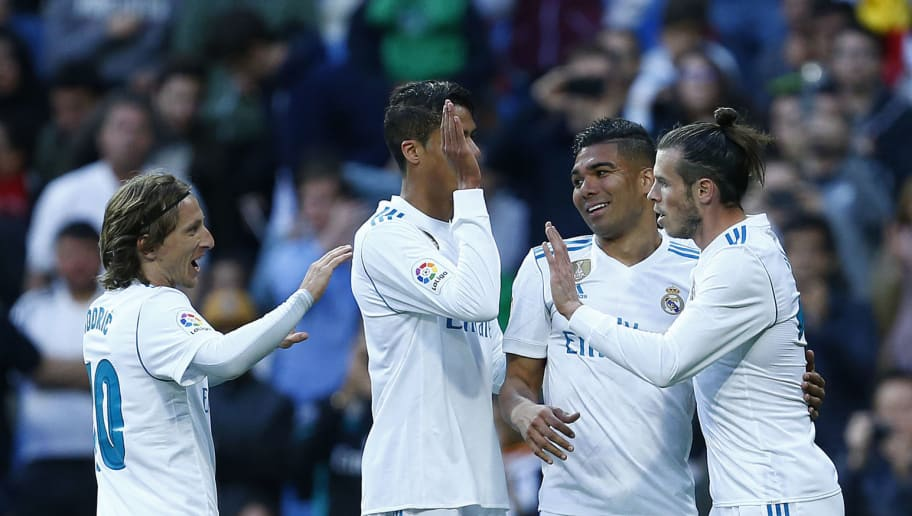 TOPSHOT - Real Madrid's Welsh forward Gareth Bale (R) celebrates a goal with teammates during the Spanish league football match between Real Madrid and Celta Vigo at the Santiago Bernabeu stadium in Madrid on May 12, 2018. (Photo by Benjamin CREMEL / AFP)        (Photo credit should read BENJAMIN CREMEL/AFP/Getty Images)