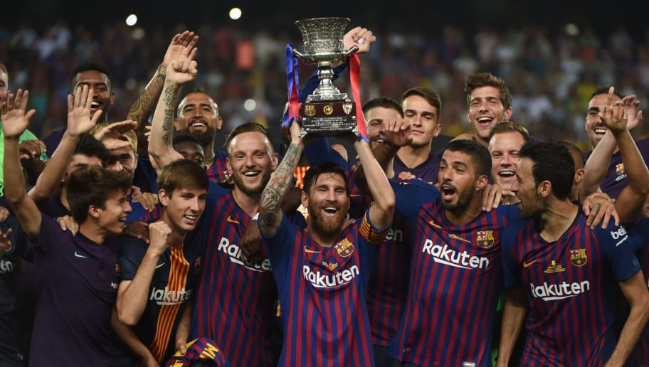 TOPSHOT - Barcelona's Argentinian forward Lionel Messi (C) carries the cup as they celebrate at the end of the Spanish Super Cup final between Sevilla FC and FC Barcelona at Ibn Batouta Stadium in the Moroccan city of Tangiers on August 12, 2018. - Barcelona defeated Sevilla 2-1 to win the Spanish Super Cup. (Photo by FADEL SENNA / AFP)        (Photo credit should read FADEL SENNA/AFP/Getty Images)