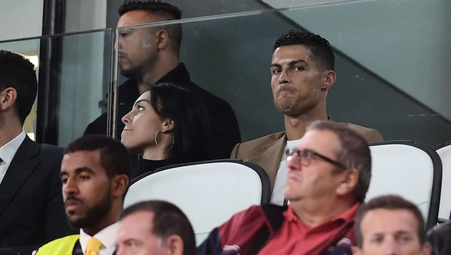 TOPSHOT - Suspended Juventus' Portuguese forward Cristiano Ronaldo (R) and his girlfriend Spanish model Georgina Rodriguez (C) watch the UEFA Champions League group H football match between Juventus and Young Boys from the tribune, on October 2, 2018 at the Juventus stadium in Turin. (Photo by Marco BERTORELLO / AFP)        (Photo credit should read MARCO BERTORELLO/AFP/Getty Images)