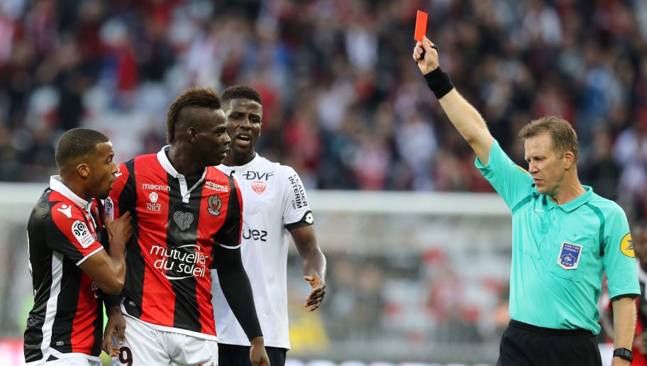 TOPSHOT - Nice's Italian forward Mario Balotelli (L) receives a red card by French referee Olivier Thual during the French L1 football match between and Dijon on November 5, 2017 at the Allianz Riviera stadium in Nice, southeastern France.   / AFP PHOTO / VALERY HACHE        (Photo credit should read VALERY HACHE/AFP/Getty Images)