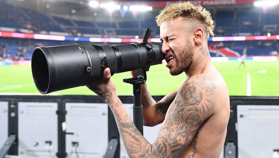 TOPSHOT - Paris Saint-Germain's Brazilian forward Neymar pretends to take pictures of his team mates as they celebrate winning the French L1 football match between Paris Saint-Germain (PSG) and Olympique de Lyon (OL) on October 7, 2018 at the Parc des Princes stadium in Paris. (Photo by FRANCK FIFE / AFP)        (Photo credit should read FRANCK FIFE/AFP/Getty Images)
