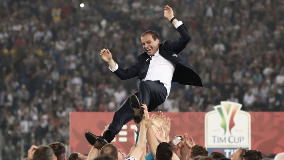 TOPSHOT - Juventus players lift Juventus' coach from Italy Massimiliano Allegri  after winning the Italian Tim Cup (Coppa Italia) final Juventus vs AC Milan at the Olympic stadium on May 9, 2018 in Rome. - Juventus crushed AC Milan 4-0 on today at the Stadio Olimpico to win a fourth consecutive Italian Cup. Mehdi Benatia opened the floodgates after 56 minutes for the first of a double of the night for the Moroccan with Douglas Costa also finding the net in the space of nine minutes. A Nikola Kalinic own goal accounted for the fourth (Photo by Isabella Bonotto / AFP)        (Photo credit should read ISABELLA BONOTTO/AFP/Getty Images)