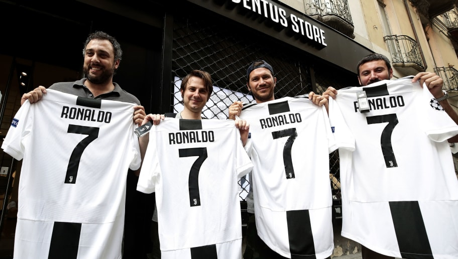 TOPSHOT - Juventus' supporters show their Cristiano Ronaldo's Juventus official Jerseys in front of the Juventus store on July 10, 2018 in Turin after Real Madrid announced today the transfer of Ronaldo to Italy's Juventus, with the Portuguese superstar saying the time had come 'for a new stage' in his life. - Real Madrid did not give any details as to the amount of the transfer but Spanish media reports have said it could reach 105 million euros ($120 million), with the 33-year-old signing a four-year contract worth 30 million euros per season. (Photo by Isabella Bonotto / AFP)        (Photo credit should read ISABELLA BONOTTO/AFP/Getty Images)