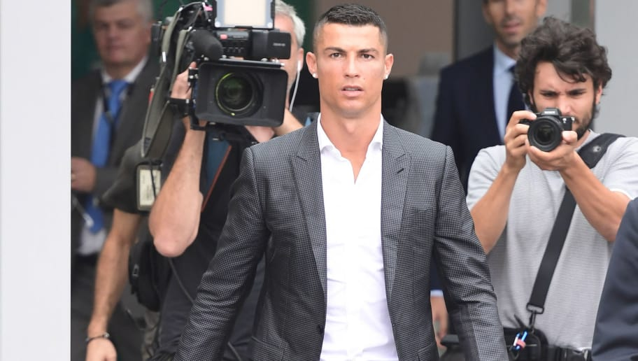 TOPSHOT - Portuguese footballer Cristiano Ronaldo (C) arrives on July 16, 2018 at the Juventus medical centre at the Alliance stadium in Turin. - A Turin hit by Cristiano Ronaldo fever awaits the striker as Juventus prepare to unveil the surprise signing, that after the end of the World Cup, puts all eyes on the Italian champions and Serie A. (Photo by Miguel MEDINA / AFP)        (Photo credit should read MIGUEL MEDINA/AFP/Getty Images)