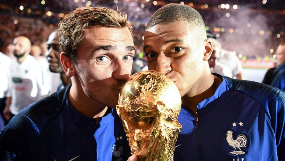 TOPSHOT - France's forward Antoine Griezmann (L) and France's midfielder Kylian Mbappe (R) kiss the 2018 World Cup trophy as they celebrate during a ceremony for the victory of the 2018 World Cup at the end of the UEFA Nations League football match between France and Netherlands at the Stade de France stadium, in Saint-Denis, northern of Paris, on September 9, 2018. (Photo by FRANCK FIFE / AFP)        (Photo credit should read FRANCK FIFE/AFP/Getty Images)