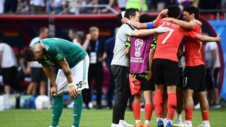 TOPSHOT - Germany's defender Niklas Suele (L) reacts next to South Korea's team players celebrating at the end of the Russia 2018 World Cup Group F football match between South Korea and Germany at the Kazan Arena in Kazan on June 27, 2018. (Photo by Jewel SAMAD / AFP) / RESTRICTED TO EDITORIAL USE - NO MOBILE PUSH ALERTS/DOWNLOADS        (Photo credit should read JEWEL SAMAD/AFP/Getty Images)