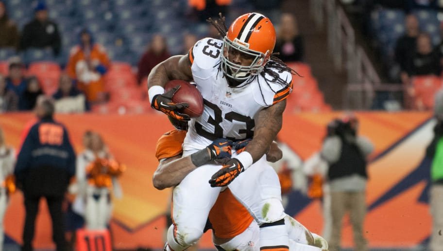 DENVER, CO - DECEMBER 23:  Running back Trent Richardson #33 of the Cleveland Browns is wrapped up as he rushes against the Denver Broncos during a game at at Sports Authority Field Field at Mile High on December 23, 2012 in Denver, Colorado. The Broncos defeated the Browns 34-12. (Photo by Dustin Bradford/Getty Images)