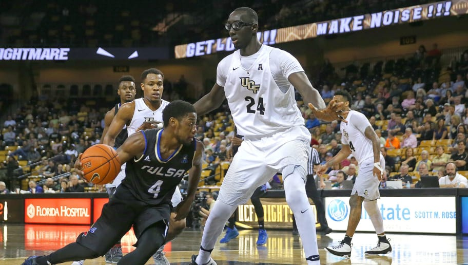 ORLANDO, FL - FEBRUARY 14:  Sterling Taplin #4 of the Tulsa Golden Hurricane drives with the ball past Tacko Fall #24 of the UCF Knights during an NCAA basketball game at the CFE Arena on February 14, 2017 in Orlando, Florida. (Photo by Alex Menendez/Getty Images)