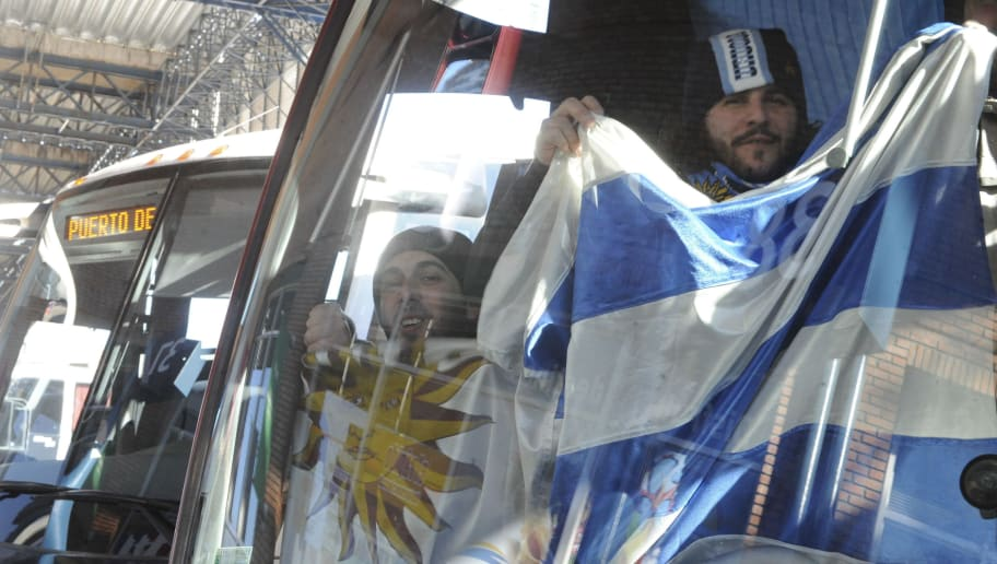 Uruguayan supporters of their national football team wave a flag from inside a bus as they depart for Buenos Aires, in Montevideo, on July 23, 2011. The Copa America 2011 final football match between Uruguay and Paraguay will e played in Buenos Aires on Sunday.  AFP PHOTO/Miguel ROJO (Photo credit should read MIGUEL ROJO/AFP/Getty Images)