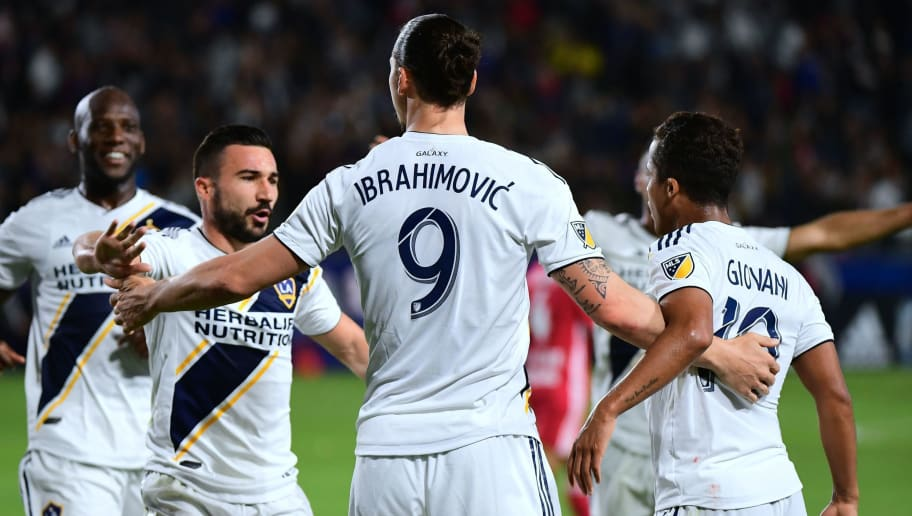 Zlatan Ibrahimovic of the LA Galaxy celebrates with teammates after his corner kick led to a goal in the second half against the New York Red Bulls in their MLS match in Carson, California on April 28, 2018. (Photo by FREDERIC J. BROWN / AFP)        (Photo credit should read FREDERIC J. BROWN/AFP/Getty Images)