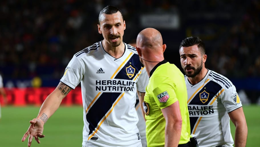 Zlatan Ibrahimovic of LA Galaxy questions a call by the referee as Romain Alessandrini looks on against the New York Red Bulls in their MLS match in Carson, California, on April 28, 2018, where New York defeated Los Angeles 3-2. (Photo by FREDERIC J. BROWN / AFP)        (Photo credit should read FREDERIC J. BROWN/AFP/Getty Images)