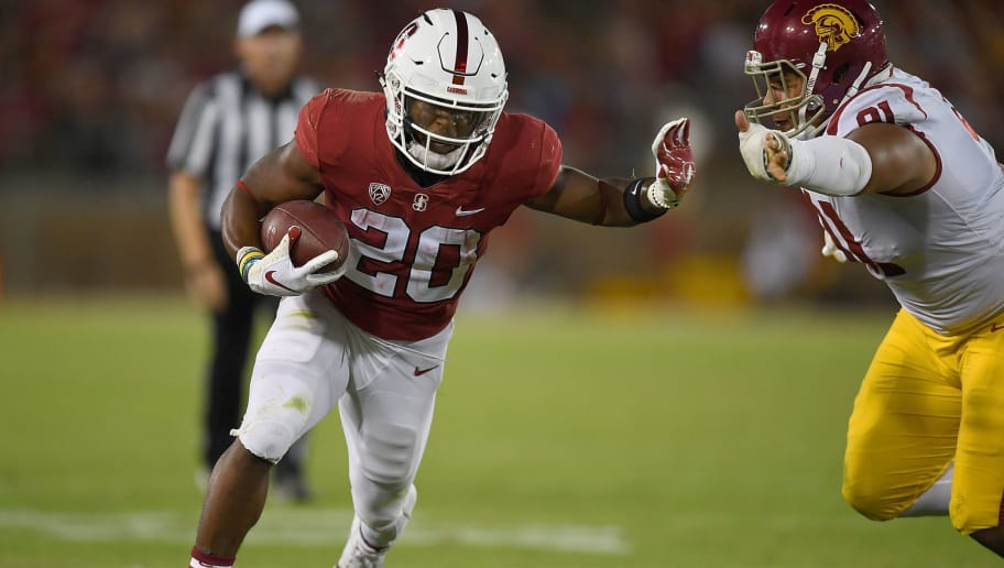 PALO ALTO, CA - SEPTEMBER 08:  Bryce Love #20 of the Stanford Cardinal runs throught the tackle of Brandon Pili #91 of the USC Trojans during the third quarter of an NCAA football game at Stanford Stadium on September 8, 2018 in Palo Alto, California.  (Photo by Thearon W. Henderson/Getty Images)