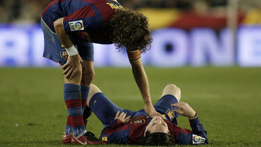 VALENCIA, SPAIN - DECEMBER 15:  Carles Puyol (L) of Barcelona comforts his injured teammate Lionel Messi laying on the pitch before abandoning the match during the La Liga match between Valencia and Barcelona at the Mestalla Stadium December 15, 2007 in Valencia, Spain. Barcelona won the match 3-0.  (Photo by Jasper Juinen/Getty Images)
