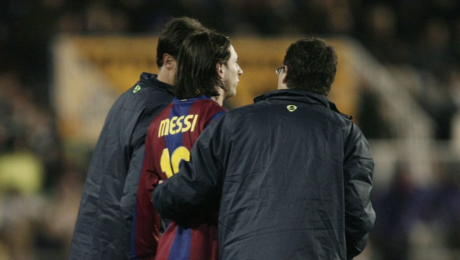 VALENCIA, SPAIN - DECEMBER 15:  Lionel Messi (C) of Barcelona is escorted off the pitch after injuring himself during the La Liga match between Valencia and Barcelona at the Mestalla Stadium on December 15, 2007 in Valencia, Spain. Barcelona won the match 3-0.  (Photo by Jasper Juinen/Getty Images)