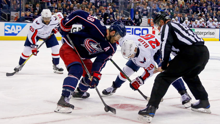 COLUMBUS, OH - APRIL 17:  Linesman Darren Gibbs #66 drops the puck for Boone Jenner #38 of the Columbus Blue Jackets and Lars Eller #20 of the Washington Capitals in Game Three of the Eastern Conference First Round during the 2018 NHL Stanley Cup Playoffs on April 17, 2018 at Nationwide Arena in Columbus, Ohio. (Photo by Kirk Irwin/Getty Images) *** Local Caption *** Darren Gibbs;Boone Jenner;Lars Eller