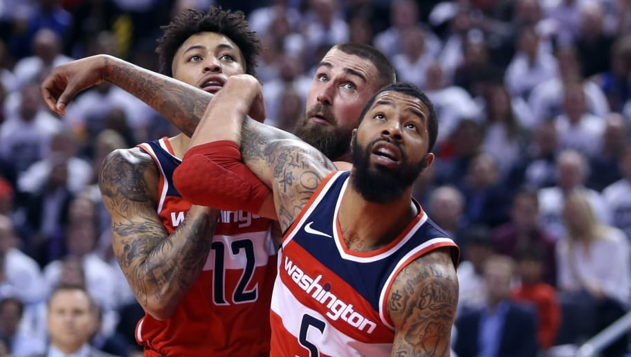 TORONTO, ON - APRIL 25:  Jonas Valanciunas #17 of the Toronto Raptors battles with Markieff Morris #5 and Kelly Oubre Jr. #12 of the Washington Wizards during the second half of Game Five in Round One of the 2018 NBA playoffs at Air Canada Centre on April 25, 2018 in Toronto, Canada.  NOTE TO USER: User expressly acknowledges and agrees that, by downloading and or using this photograph, User is consenting to the terms and conditions of the Getty Images License Agreement.  (Photo by Vaughn Ridley/Getty Images)