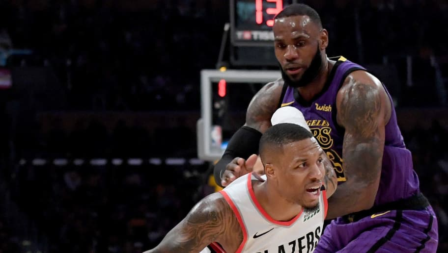 LOS ANGELES, CA - NOVEMBER 14:  Damian Lillard #0 of the Portland Trail Blazers drives past LeBron James #23 of the Los Angeles Lakers at Staples Center on November 14, 2018 in Los Angeles, California.  NOTE TO USER: User expressly acknowledges and agrees that, by downloading and or using this photograph, User is consenting to the terms and conditions of the Getty Images License Agreement.  (Photo by Harry How/Getty Images)