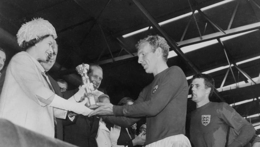 Queen Elizabeth of England presents the Jules Rimet Cup to Bobby Moore, captain of England's national soccer team, as her husband Prince Philip (C) and forward Geoff Hurst (R) look on after England beat West Germany 4-2 in extra time in the World Cup final 30 July 1966 at Wembley stadium in London. Hurst scored three goals, two of them in extra time, to help England win its first World title. AFP PHOTO / AFP PHOTO / STAFF        (Photo credit should read STAFF/AFP/Getty Images)
