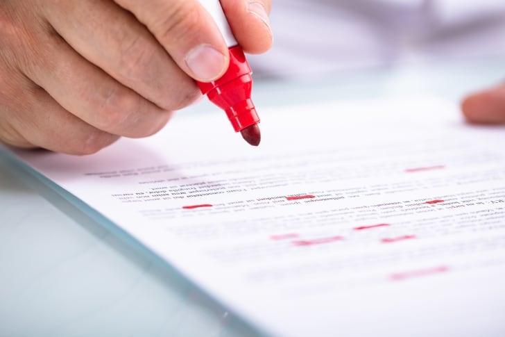 A hand holding a red pen and marking up a document