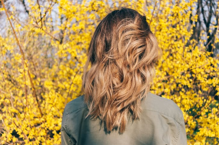 Blond woman facing forsythia bush