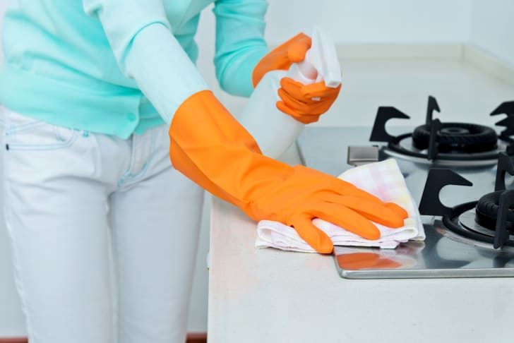 woman cleaning a kitchen range