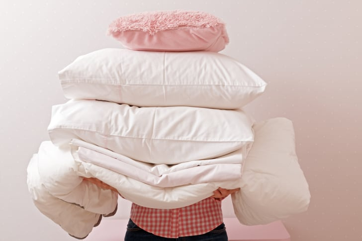 person carrying a pile of pillows