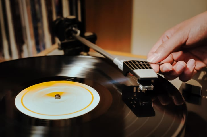 A woman with her hand on the record player