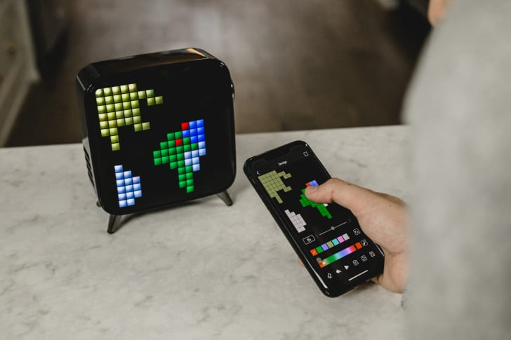 Person using phone to program a pixel art display on the Tivoo-Max smart speaker