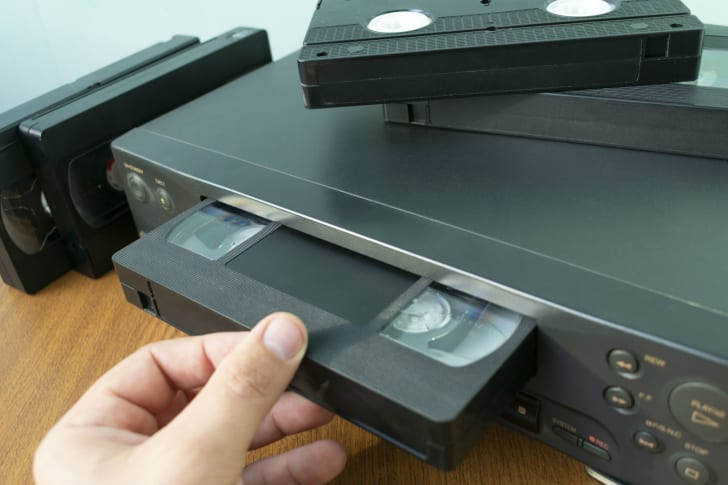 A VHS cassette tape is inserted into a VCR