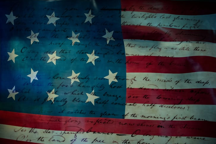 """The lyrics of """"The Star-Spangled Banner"""" superimposed on an old American flag."""