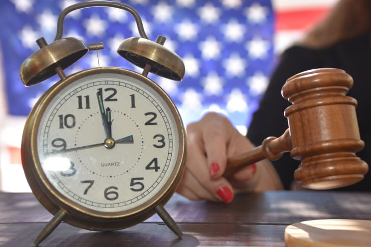 A photo of a judge handing out a sentence with a clock sitting next to her