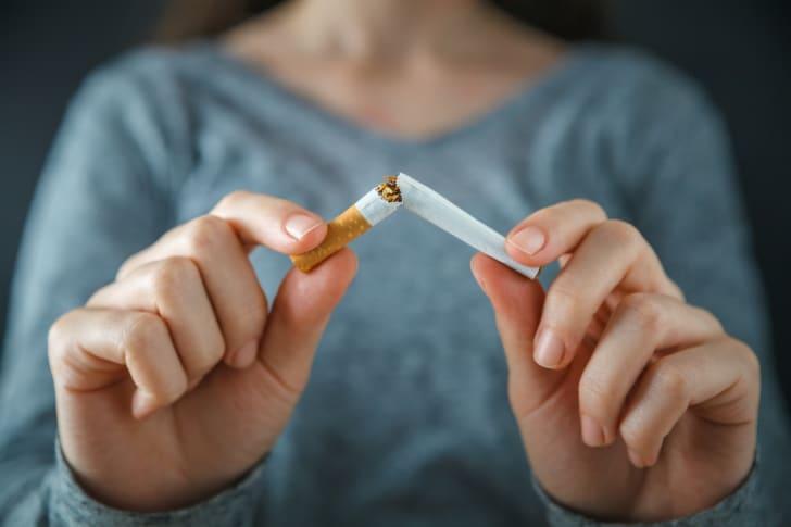 A woman breaks a cigarette in half.