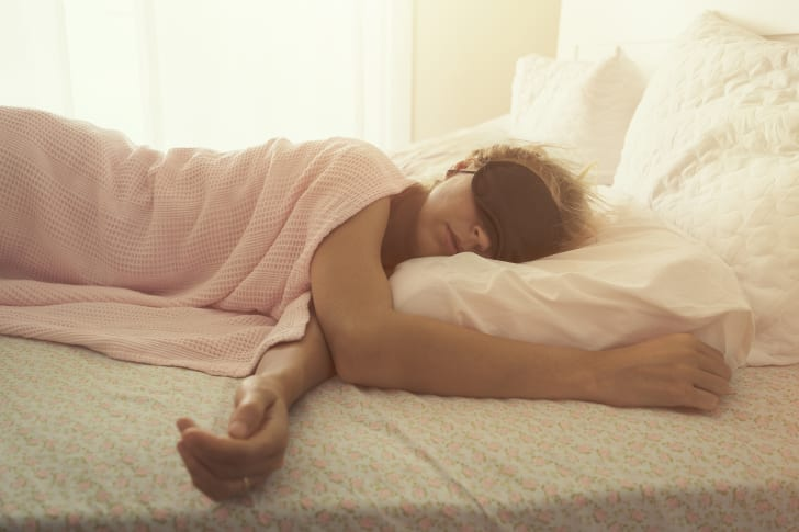 A woman wearing an eye mask sleeps on white sheets